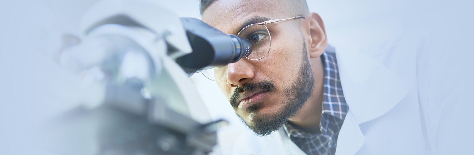 Man in white uniform looking through microscope