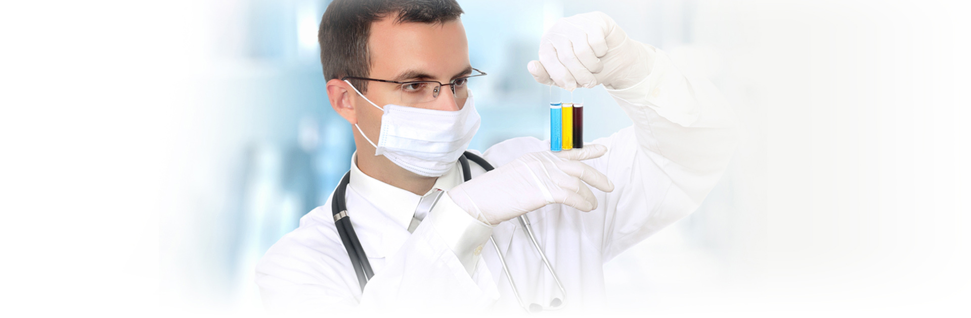 Doctor with mask holding up three different color fluids in test tubes