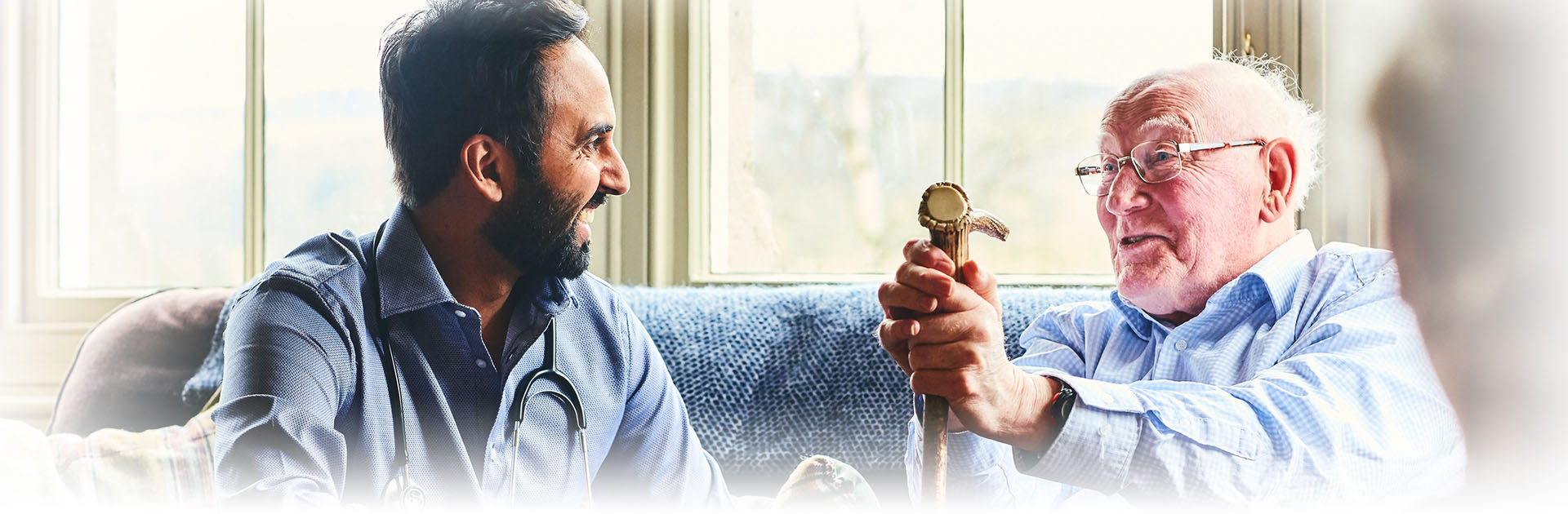 two men sitting on the couch laughing, one holds a walking stick