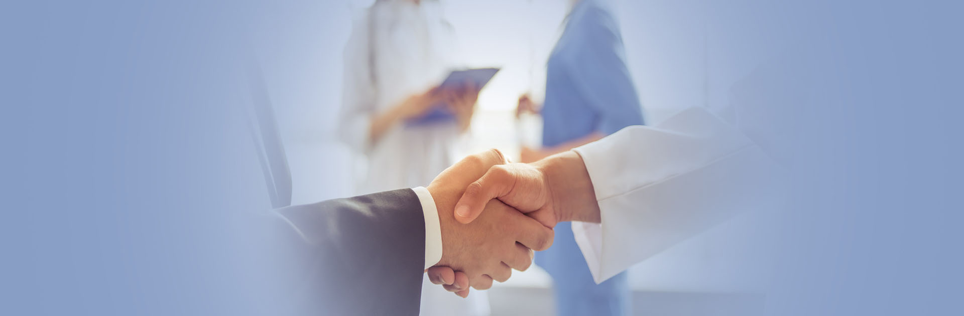 Man in suit shaking hands with man in white doctors uniform.