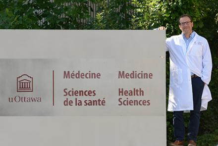 Dr. Lacoste standing beside uOttawa campus sign